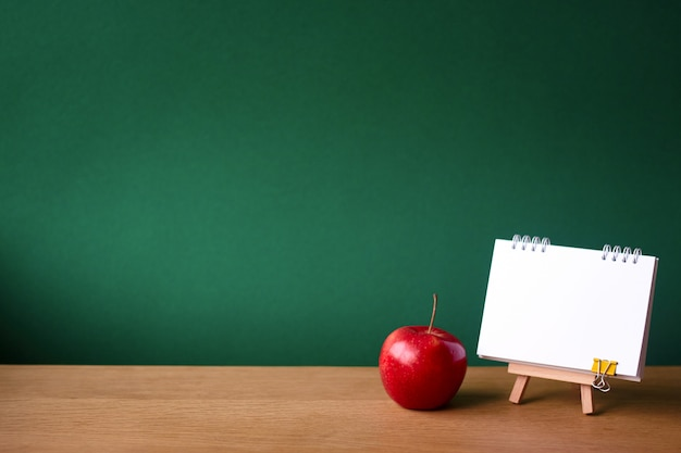 Back to school with open notebook on miniature easel and red apple on wooden surface