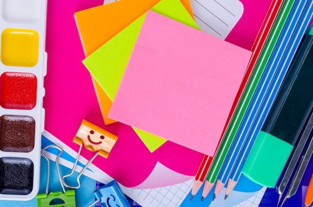Back to school with schools accessories - paints, pencils, notebooks, scissors, markers, blue.