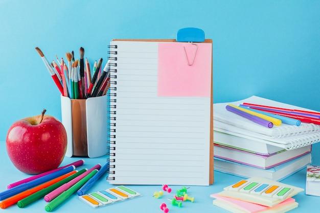 Back at school, work, workplace of a schoolchild stationery, notebooks on blue