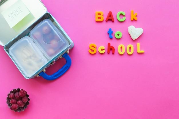 Back to school writing near lunchbox and raspberries