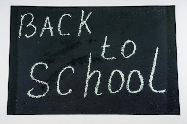 Back to school written in chalk on a black chalkboard