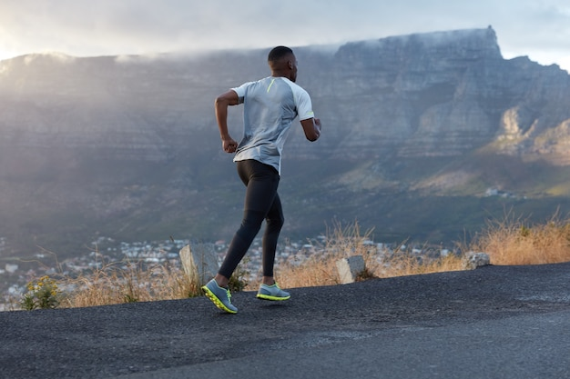 Back shot of active dark skinned man being in action, runs across mountain road, leads healthy lifestyle, has endurance and motivation to be fit, poses over mountain, enjoys nature