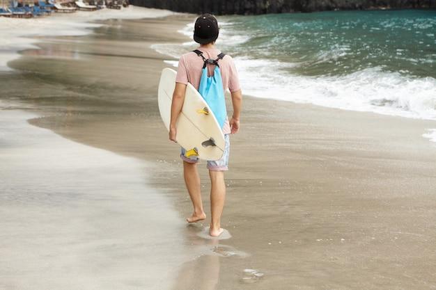Colpo posteriore del surfista alla moda con la borsa blu che trasporta la sua tavola da surf bianca