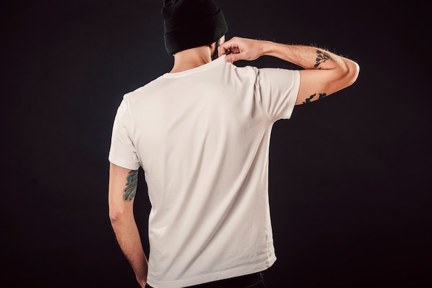 Back shot of handsome bearded man with fresh haircut and tattooed arms posing on isolated wall mockup in white simple blank tshirt ready for designs