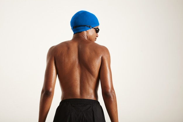Back shot of the muscular wet back of a young strong african american swimmer in blue cap