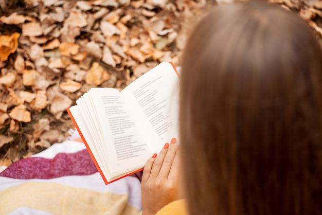 葉や草の上に座って色とりどりの秋の公園でいくつかの詩を読んでいる女の子のバックショット