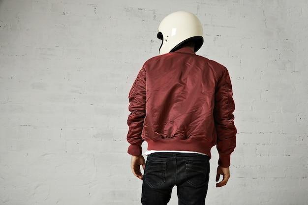 白いヘルメットと白で隔離のバーガンディボンバージャケットのモーターサイクリストのバックショット