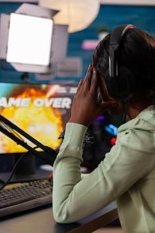 헤드폰을 끼고 가상 경쟁에서 지는 아프리카계 미국인 e스포츠 스트리밍의 백샷. 강력한 컴퓨터에서 새로운 그래픽으로 온라인 비디오 게임을 스트리밍하는 전문 게이머.