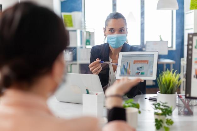 会社のオフィスに座ってタブレットコンピューターを使用して管理プレゼンテーションで一緒に働いている医療フェイスマスクを持つビジネス女性のバックショット。社会的距離を尊重するチーム。
