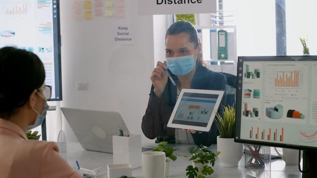 会社のオフィスに座ってタブレットコンピューターを使用して管理プレゼンテーションで一緒に働いている医療フェイスマスクを持つビジネス女性のバックショット。社会的距離を尊重するチーム