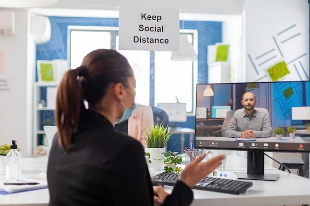 Назад выстрел деловой женщины в медицинской маске, говорящей на видеозвонке с удаленной командой. исполнительный фрилансер, работающий в новом обычном офисе компании во время пандемии коронавируса.
