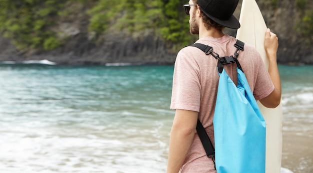 Задний снимок кавказского человека с синей сумкой, держащего доску для серфинга, смотрящего на своих друзей, занимающихся серфингом, катающихся на гигантских волнах в ветреный летний день