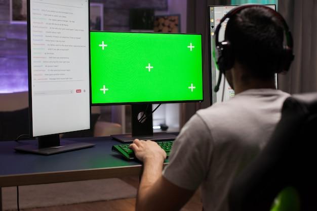 夜遅くに緑のモックアップでコンピューター上でオンラインゲームをプレイしている競争力のある若い男のバックショット。