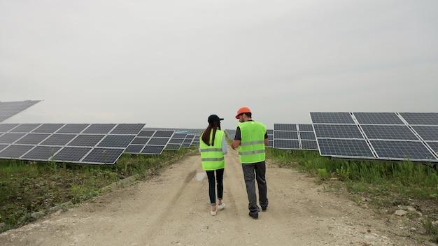 특별한 제복을 입고 태양 전지판을 검사하는 엔지니어 남녀의 백샷은 전기 엔지니어 환경에서 햇볕이 잘 드는 배터리 설치에 대해 논의합니다. 청정 에너지 생산