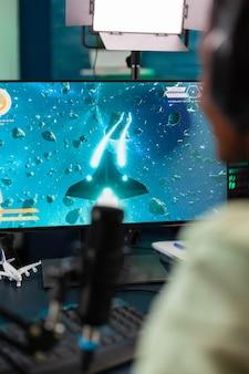 라이브 토너먼트 중 스페이스 슈터 게임을 하는 e스포츠 스트리머의 백샷. 온라인 챔피언십을 위해 헤드폰과 키보드를 사용하여 재미를 위해 바이러스성 비디오 게임을 스트리밍합니다.