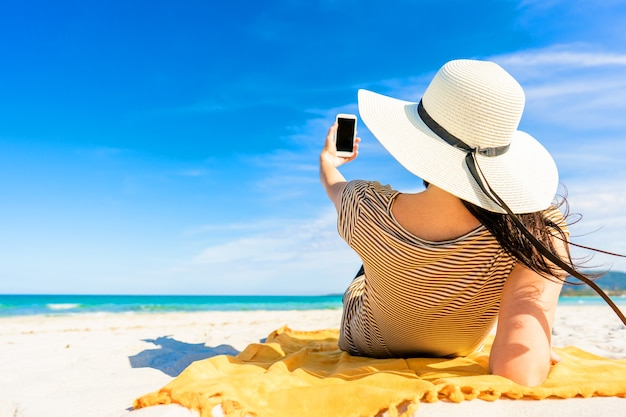 熱帯のビーチの砂の上に横たわっている大きな白い帽子をかぶったファッショナブルな若い認識できない女性のバックショットは、ソーシャルネットワークで休暇を共有するスマートフォンで自分撮りをしています。明るく鮮やかなカラー写真