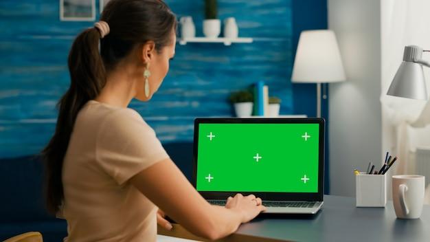 녹색 화면 크로마 키 디스플레이가 있는 격리된 pc를 사용하여 마케팅 프로젝트에서 일하는 프리랜서의 백샷. 홈 오피스 스튜디오에 앉아 노트북 컴퓨터에 입력하는 여자