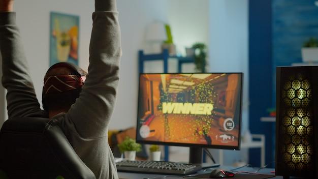 強力なパソコンでプレイしている一人称シューティングゲームのビデオゲームに勝つ幸せな男のゲーマーのバックショット。テクノロジーネットワークワイヤレスを使用したゲームトーナメント中のオンラインストリーミングサイバーパフォーマンス