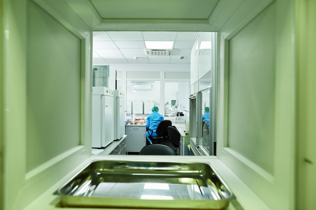 Задний снимок ученого-медика в защитном костюме и одноразовой медицинской шляпе, работающего в лаборатории