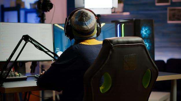 홈 스튜디오에서 rgb 키보드를 사용하여 1인칭 비디오 게임을 하는 프로 게이머 여성의 뒷모습. 온라인 경쟁 중 전문 게임용 강력한 컴퓨터를 사용하여 게이머 스트리밍 게임 플레이