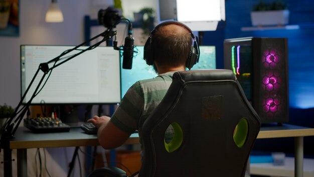 トーナメント用の強力なコンピューターシューティングビデオゲームで遊んでいるストリーマーの男性のバックショット。複数のプレーヤーとヘッドフォンで話している。プロのストリーミング機器を使用したプロのビデオゲームr