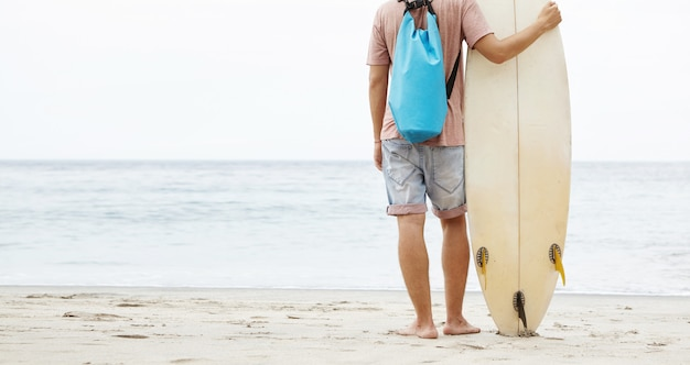 Задний снимок молодого босого кавказского серфера, стоящего на песчаном пляже, опираясь на доску для серфинга и любуясь красотой и мощью океана перед ним
