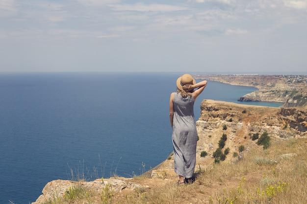 Задний план молодой женщины в элегантном платье, любуясь захватывающим дух видом, стоя на самом краю вершины горы, лицом к бескрайнему синему океану, держа соломенную шляпу на голове из-за ветра