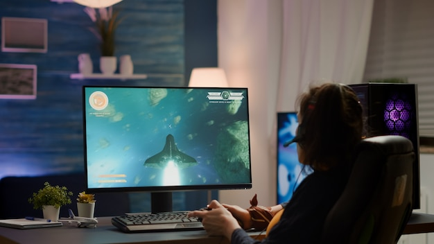 Back shot of pro gamer playing online space shooter game on powerful computer using wireless controller. competitive cyber player woman performing video game tournament use professional joystick
