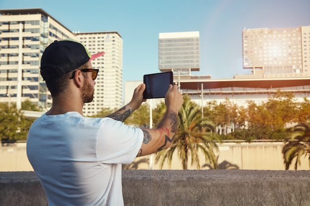 Back shot of a young man in plain white t-shirt and baseball hat taking a photo of city buildings and palm trees on his tablet.