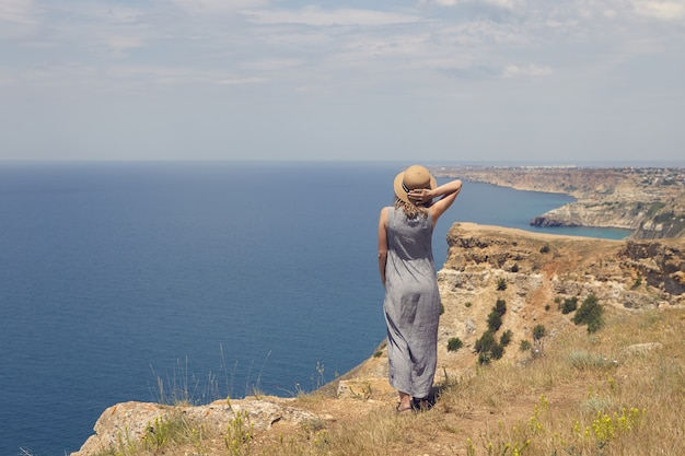 Back shot of young woman in elegant dress admiring breathtaking view while standing on very edge of mountain top, facing vast blue ocean, holding straw hat to keep it on her head because of wind