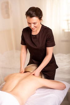 Back and shoulder massage by a physiotherapist who is smiling