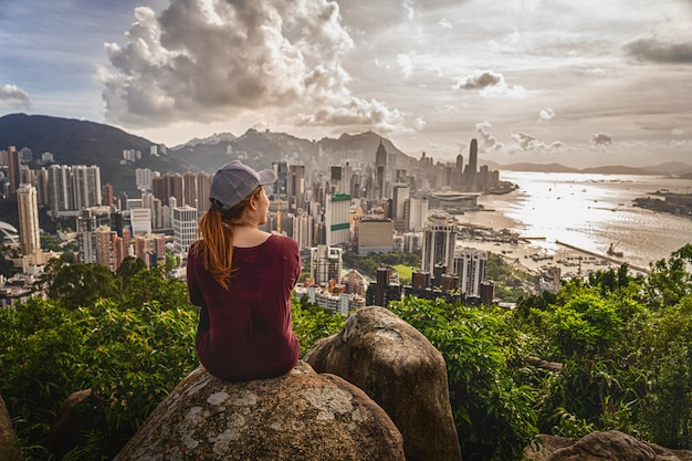 Back side of asia woman traveler sitting after climbing the peak of hong kong mountain and looking hong kong and kowlloon cityscape when sunset time, adventure