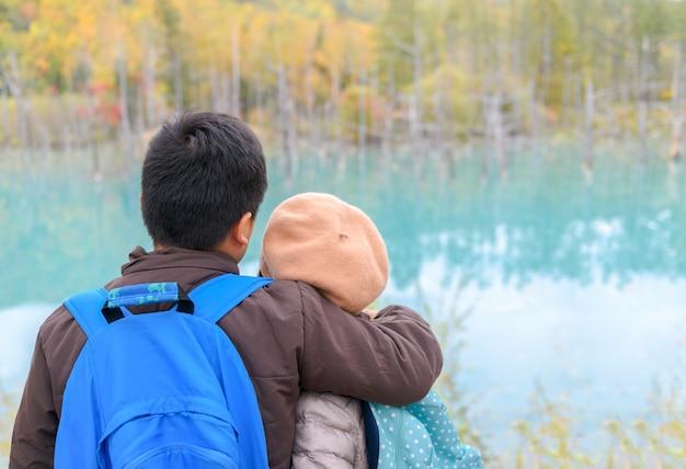 Back side of brother hugging sister at blue pond