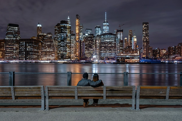 Back side couple sitting and looking new york cityscape beside the east river at the night time