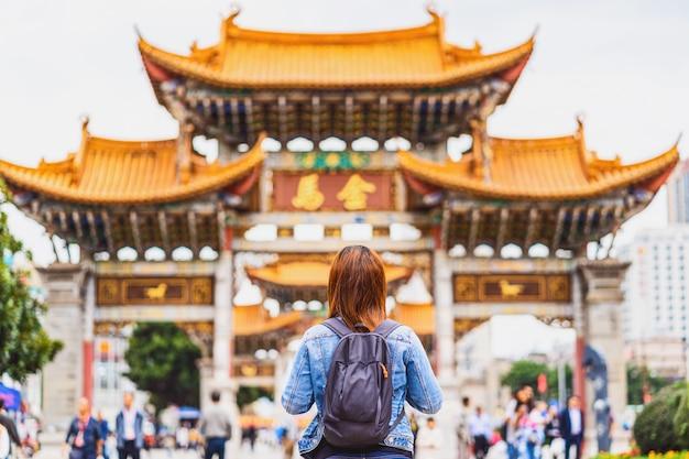 アジアのバックパッカーの女性の裏側は、中国の昆明、金美広場を旅行しているとき、旅行、観光、中国文化、伝統的な有名な場所、ランドマークコンセプト