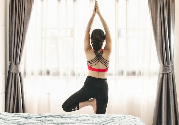 Covid19の発生時に寝室で自宅からヨガを練習しているアジアの女性の裏側