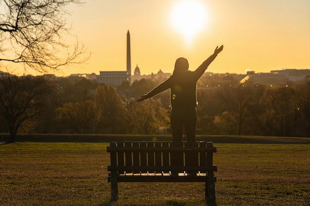 立っているアジアの女性の裏側とワシントンdcのランドマークで成功するための手を持ち上げ