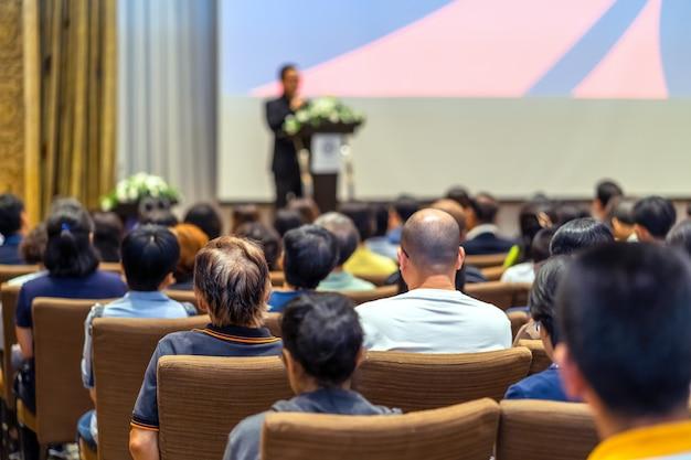 컨퍼런스 홀의 무대에서 연단이 있는 스피커를 듣고 있는 청중의 뒷면