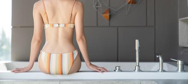 Задняя сторона женщины бикини, сидящей на стороне белой ванны в ванной комнате.