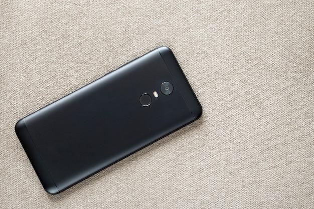 보안 엄지 지문 스캔 장치 및 가벼운 천으로 플래시 조명에 플래시 조명 절연 검은 핸드폰의 뒷면. 현대 기술과 스마트 폰 디자인 컨셉입니다.