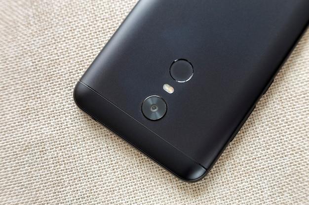 가벼운 천으로 복사 공간 배경에 보안 엄지 지문 스캐닝 장치, 카메라 및 플래시 조명으로 격리 검은 핸드폰의 뒷면. 현대 기술과 스마트 폰 디자인 컨셉입니다.