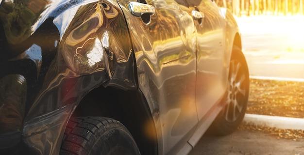 도로에서 사고로 파손되고 부서진 검은색 자동차의 뒷면