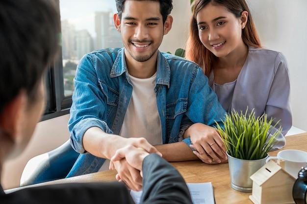 Задняя сторона рукопожатия между продавцом и владельцем дома при знаке контакта