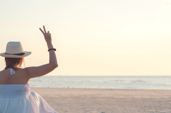 Back side of happy woman sitting summer beach showing two fingers or victory sign.