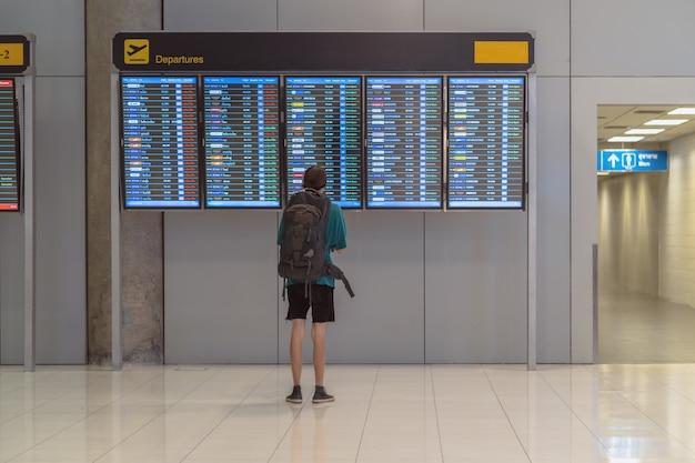 チェックインのためにフライトボードの上に荷物を持って立っている旅行者の裏側