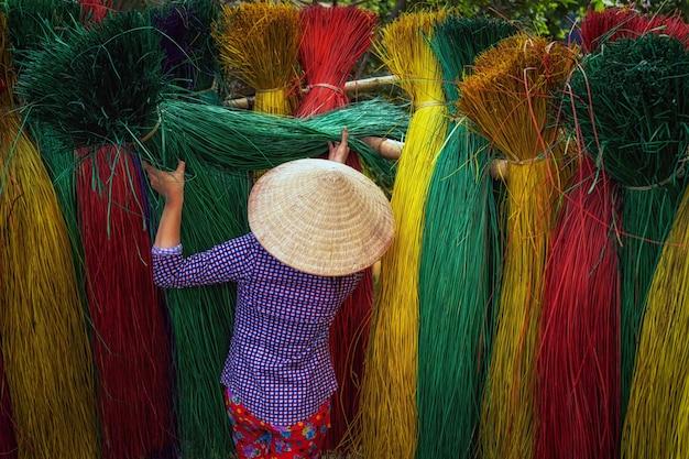 오래된 전통에서 전통 베트남 매트를 건조하는 베트남 여성 장인의 뒷면