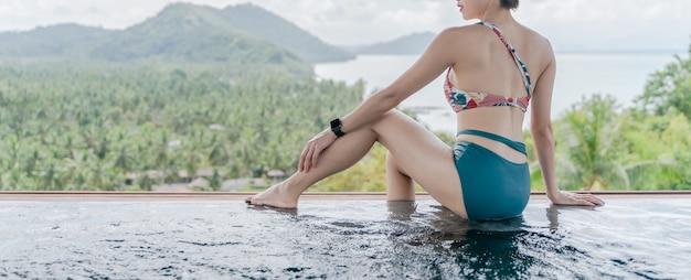 Задняя сторона женщины в зеленом купальнике, сидящей на краю пейзажного бассейна с видом на горы и океан.