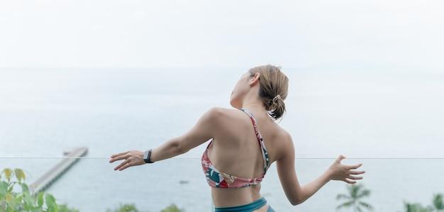 Задняя сторона женщины в купальнике, размещая на стеклянном прозрачном балконе с видом на океан.