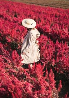 赤い花畑を歩いているトレンチコートと麦わら帽子の女性の裏側。