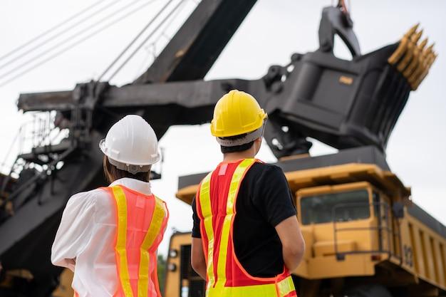 Задняя сторона рабочих на добыче лигнита или угля с грузовиком, перевозящим уголь.